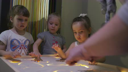 puericultura : children draw pictures with sand on specially lit table