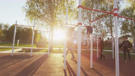 horizontal bar : boy and guys train on horizontal bar on city sports ground Stock Footage