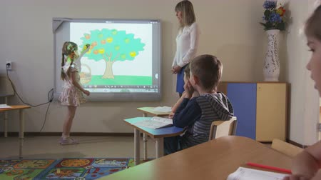 small pen : small girl stands at whiteboard in kindergarten at lesson