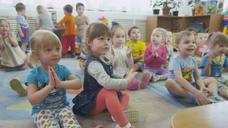 girl claps : children clap hands after puppet show in kindergarten