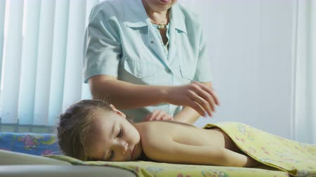 поясница : nurse in blue coat does massage to blond girl in light room