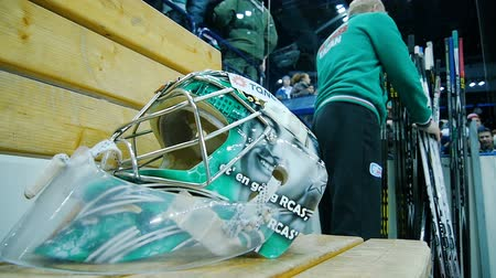 hokej : slow motion close goalkeeper helmet with mask on wooden bench