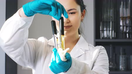 chemical agent : girl twists flasks caps with chemical agent in laboratory