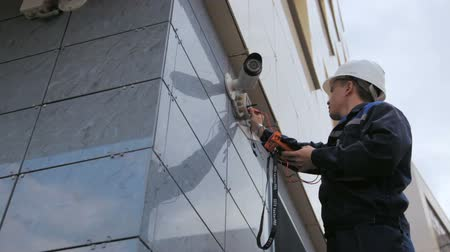 television set : worker adjusts videcam mounted on building wall with instrument