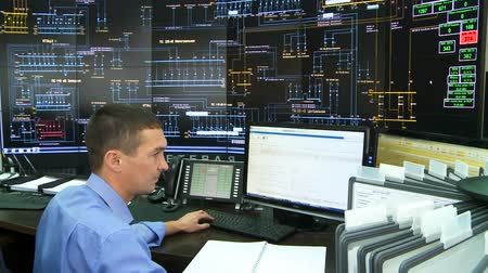 estrutura construída : engineer works at monitor in control centre with schemes on wall screens