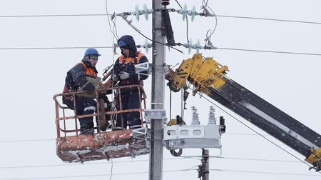 floodlight : workers mount wires on pole from hanging crane cradle on frosty day