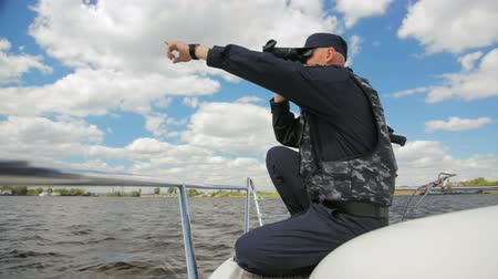 patrol : water policeman sits on motorboat monitoring river through binoculars