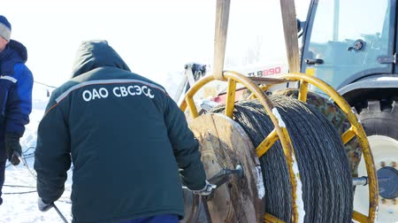 přadeno : workers fasten steel wire rope coil near tractor in winter