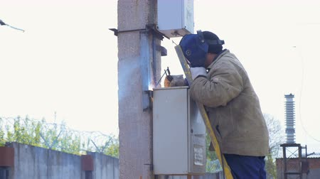 pilon : worker in helmet welds switchboard on pole under grey sky Stock mozgókép