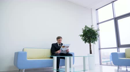 jornal : man in formal suit sits in office hall reads newspaper waits for manager