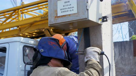 lineman : worker welds up switchboard to pole at construction site