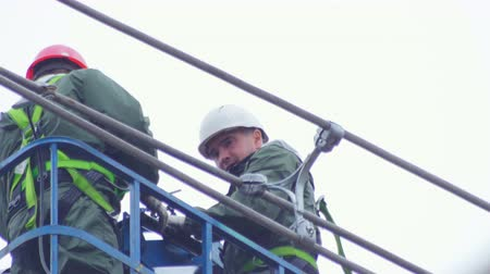 lineman : technicians fix transmission wires overhead on ground Stock Footage