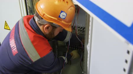 elektryk : close electrician with beard mends equipment in switchgear case