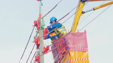 фиксировать : electricians in cradle fix metal wire support on pole