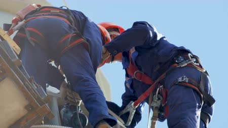 lineman : workers fix equipment on electric tower against blue sky Stock Footage