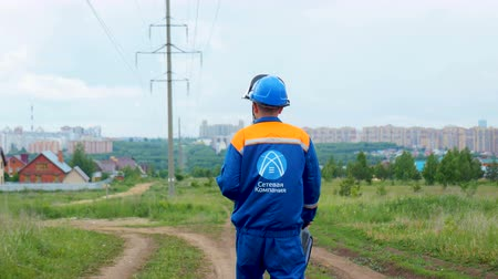 зад : worker walks to distant village with electric post Стоковые видеозаписи