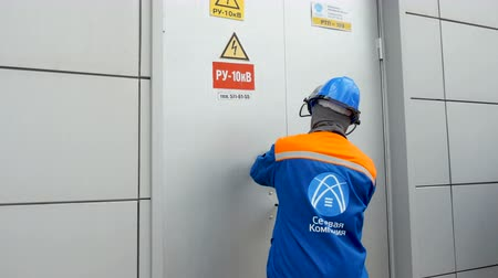 прерыватель : technicians go out from electrical station premises close door Стоковые видеозаписи