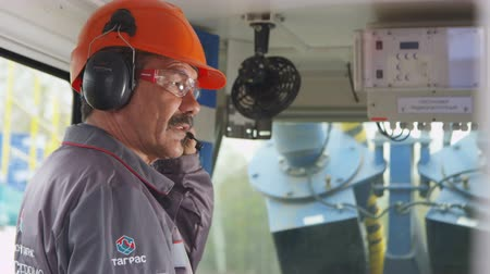 bigode : worker in helmet and headphones with microphone speaks in cabin