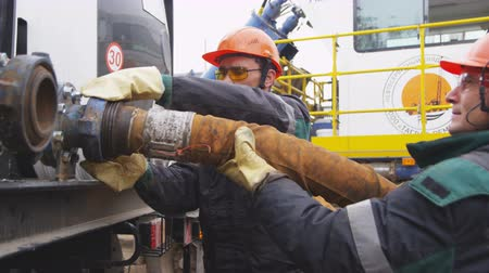 клапан : employees connect thick hose to drilling machine at prospecting site Стоковые видеозаписи