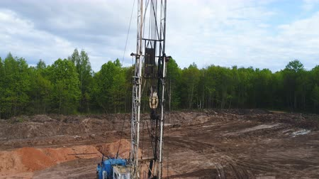 alapítvány : drilling machine pipes on truck platform on ground with workers by forest