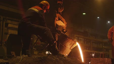 blast furnace : skilled technician turns lever of bucket with molten metal