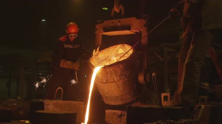 fornalha : skilled employees pour red metal in workshop Vídeos