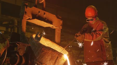 temprature : worker turns bucket and metal pours against darkness