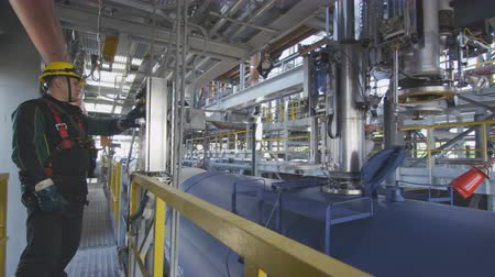 distillation tank : modern petrochemical plant and employee at control panel