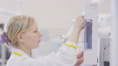 produtos químicos : blond girl in white robe does experiments on equipment in lab