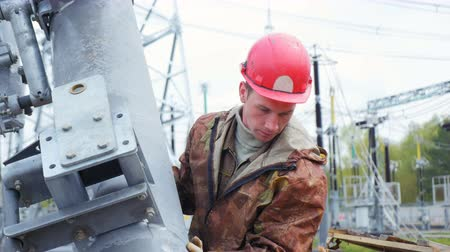 direct current : worker holds metal tower pipe to mount on transformer substation