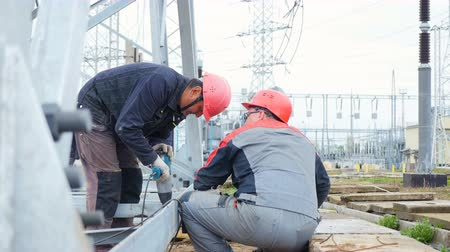 condutor : workers operate with electric drill on transformer substation building site