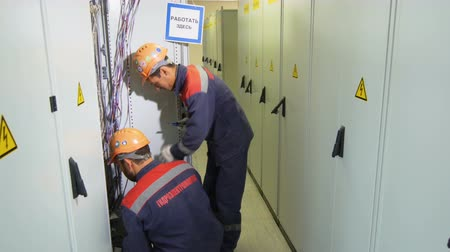 tester : electricians with company logo check equipment in switchgear case in corridor