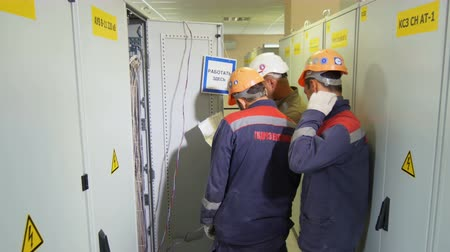 tester : side view technicians discuss problem near network power cabinets
