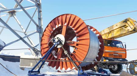 přadeno : KAZAN, TATARSTAN  RUSSIA - MAY 23 2018: Huge steel wire rope hank uncoils on transformer substation building site near truck crane on winter frosty day on May 23 in Kazan