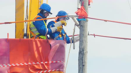 fitter : employees operate with electric cable on wooden pole in crane cradle