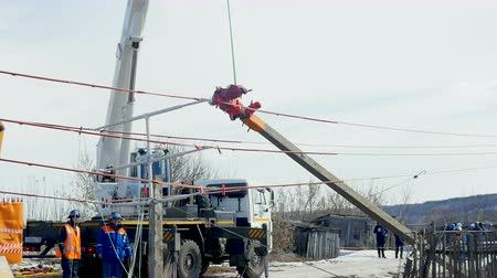levantado : electric pole lifted up with crane hook by village in winter