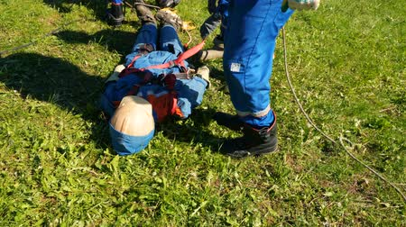 lineman : workers rescue electricity victim mannequin at pole on grass Stock Footage