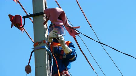 fitter : employee operates with electric wires on post under blue sky Stock Footage