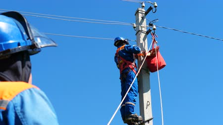 fitter : electricians fix electric cable on post against blue sky