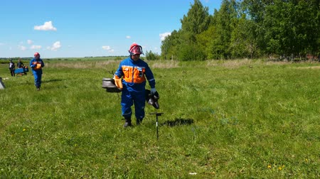 konkurenti : competitor with pairs of rubber boots walks across field squats near peg Dostupné videozáznamy
