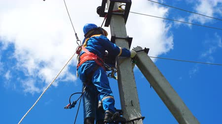 fitter : electrician-fitter climbs pole with leg-irons holding mannequin rescueing