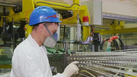 příze : employee in workwear respirator controls thread moving direction though holes