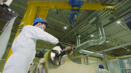 дополнительный : employee removes extra lubrication from machine rotating shaft at factory