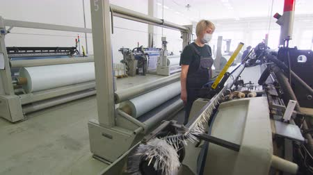 moinho : woman monitors looms operation at synthetic fabric manufacturing factory