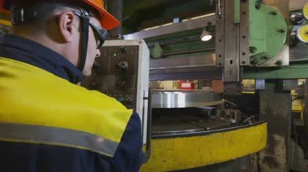 bum : backside view worker near machine grinding round detail Stock Footage