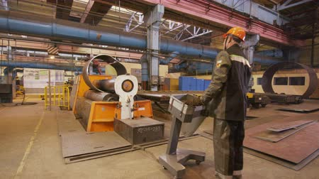 controles : operator controls machine bending metal sheet to tube at plant
