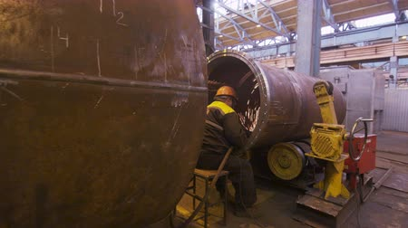 chuveiro : motion to middle-aged welder working with huge tube under sparks