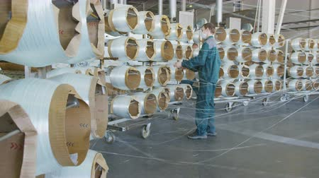 углерод : employees in masks monitor fiberglass bobbins unwinding to produce materials Стоковые видеозаписи