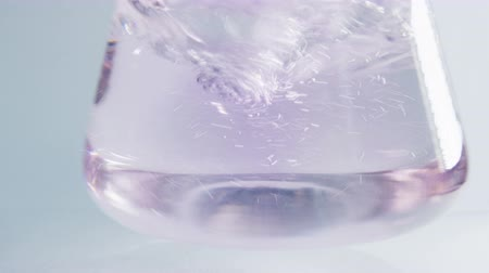 banka : closeup clear liquid shaken in lab bulb by hand becomes pink Dostupné videozáznamy