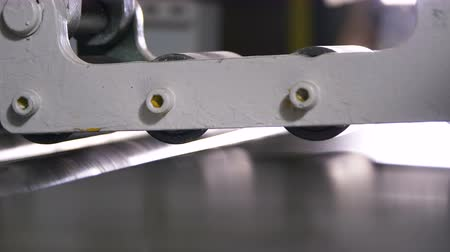 pivovar : closeup thin metal sheets move between rotating rolls Dostupné videozáznamy